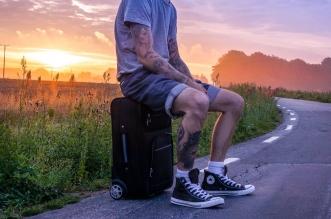 sentado en su maleta